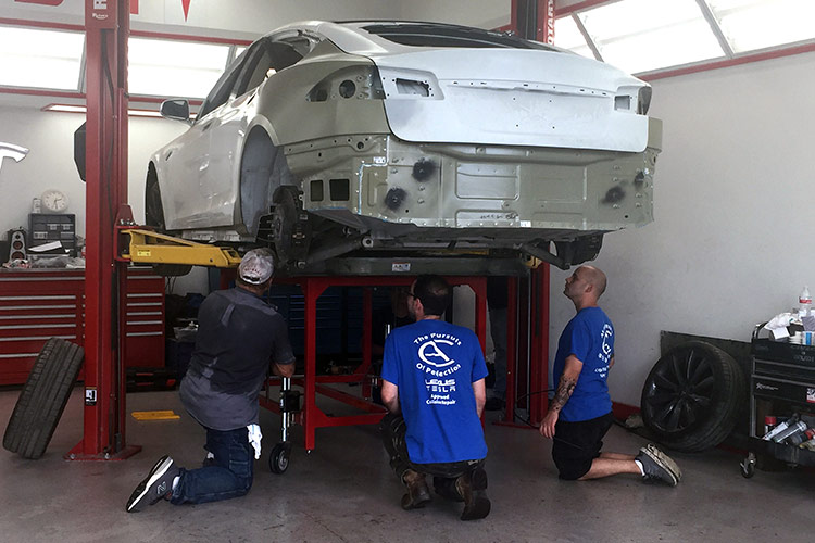 Reviewing undercarriage damage on Tesla Motors vehicle on car lift at Autocraft Bodywerks