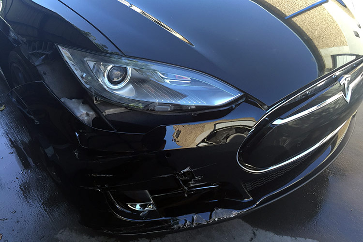 Front right quarter panel collision damage to a Tesla vehicle being repaired at Autocraft Bodywerks