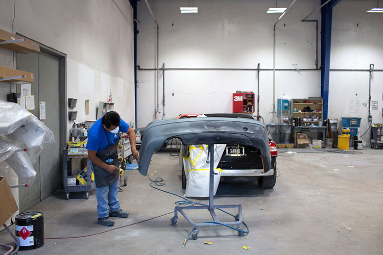 Repairing damaged rear car bumper in the body shop at Autocraft Bodywerks
