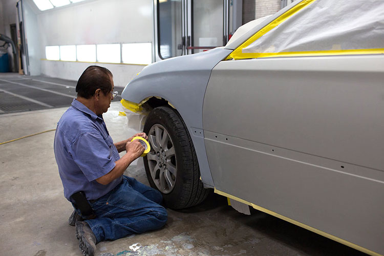 Taping a repaired vehicle before heading into the painting booth for expert color matching